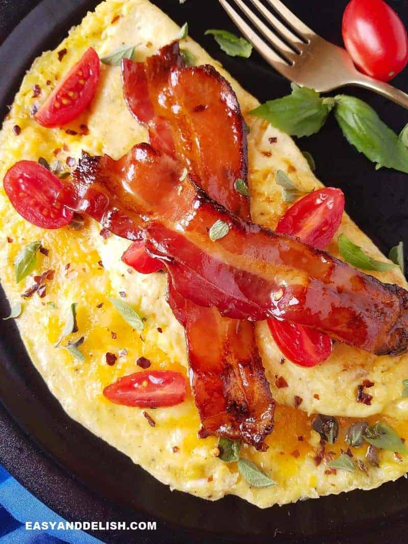 close up of an easy omelette filled with cheese and topped with bacon and herbs