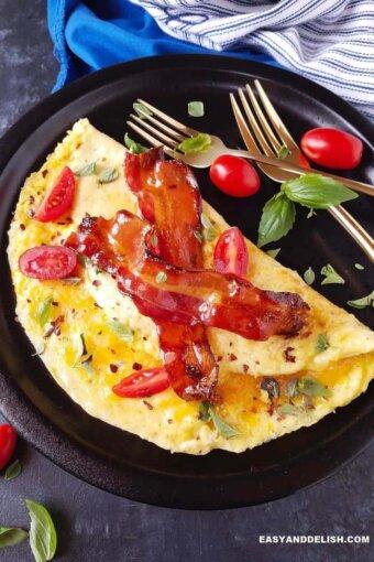 omelete simples em um prato com queijo, bacon e verduras