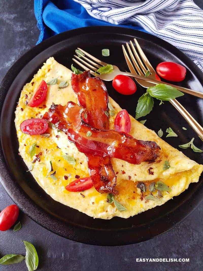 omelete simples em um prato com bacon e verduras