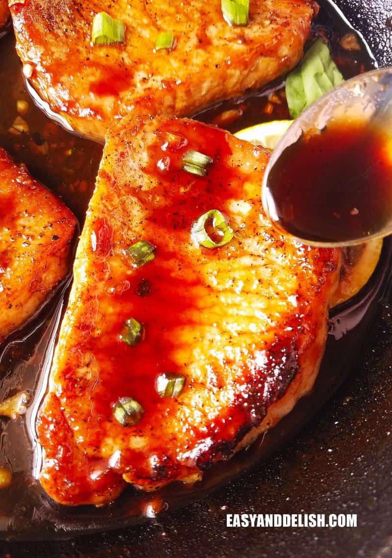 close up image of pan-seared pork chops about to be drizzled with sauce