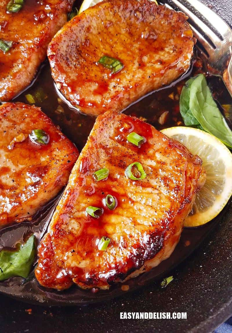 several chops in a pan garnished with lemon slices