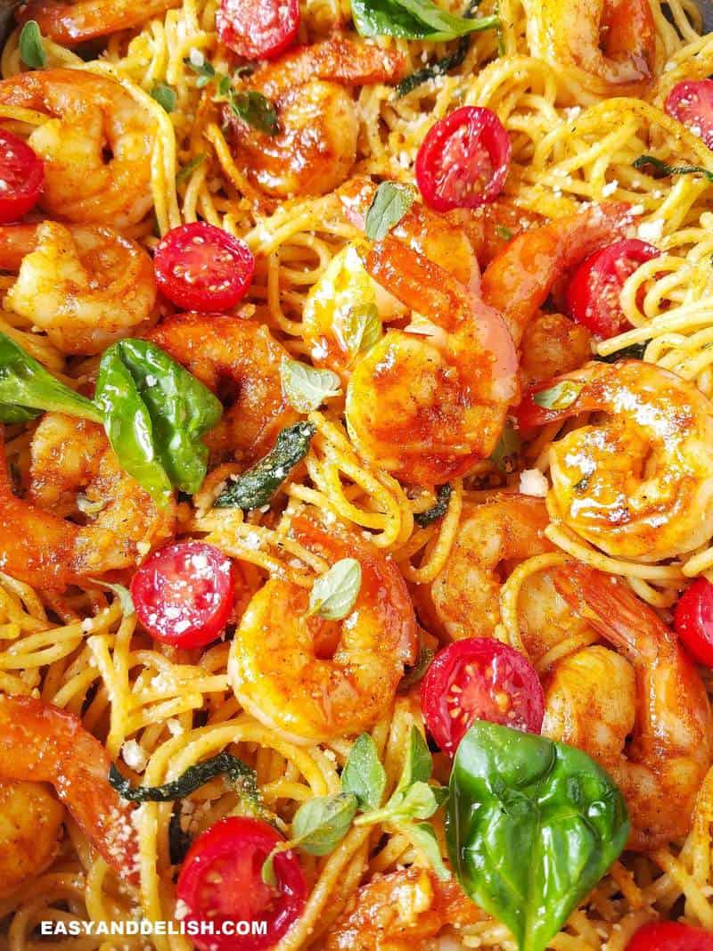 close up of shrimp spaghetti with spinach and tomatoes