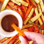 roasted carrots and parsnips being dipped in a dressing