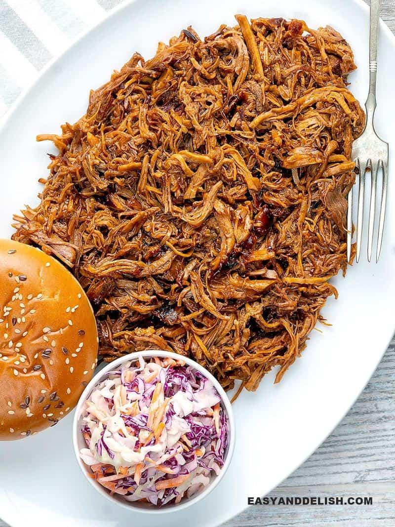 carne de porco desfiada em uma travessa com pão e salada