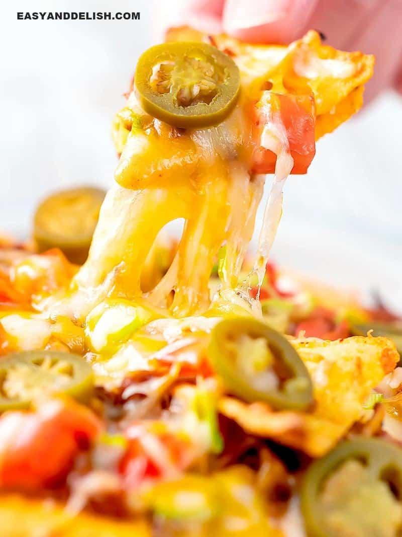 nachos sendo puxados com queijo derretido