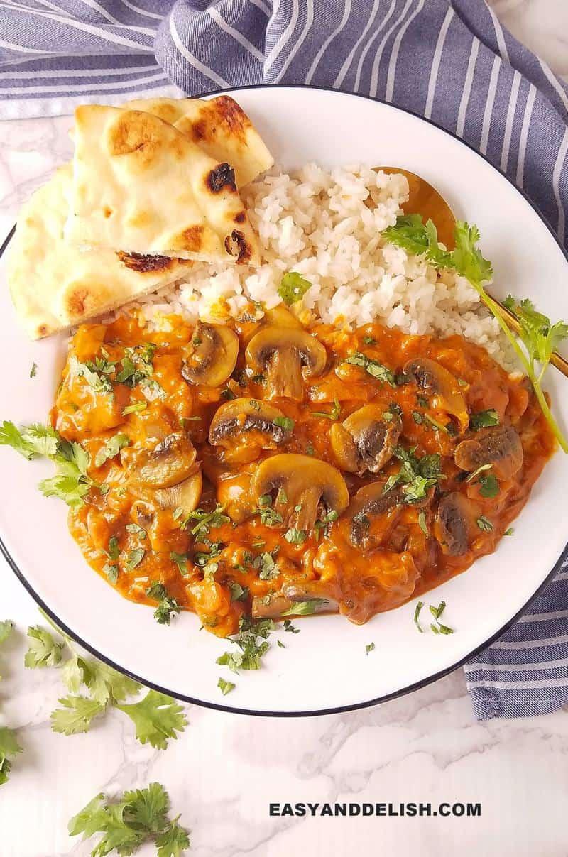 um prato de guisado sobre arroz e pão ao lado
