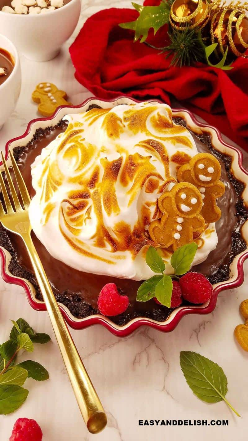 chocolate meringue pie with a fork on the side and Christmas decorations