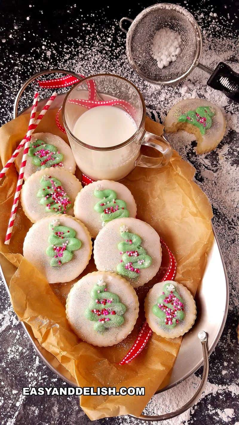 cookies decorado de natal em um prato com uma xícara de leite ao lado