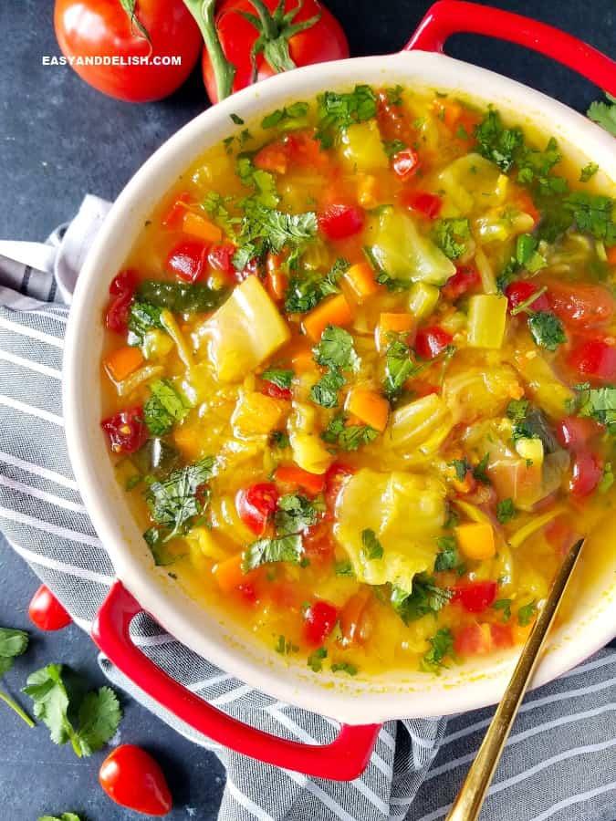 uma tigela de sopa de repolho para emagrecer com verduras ao lado