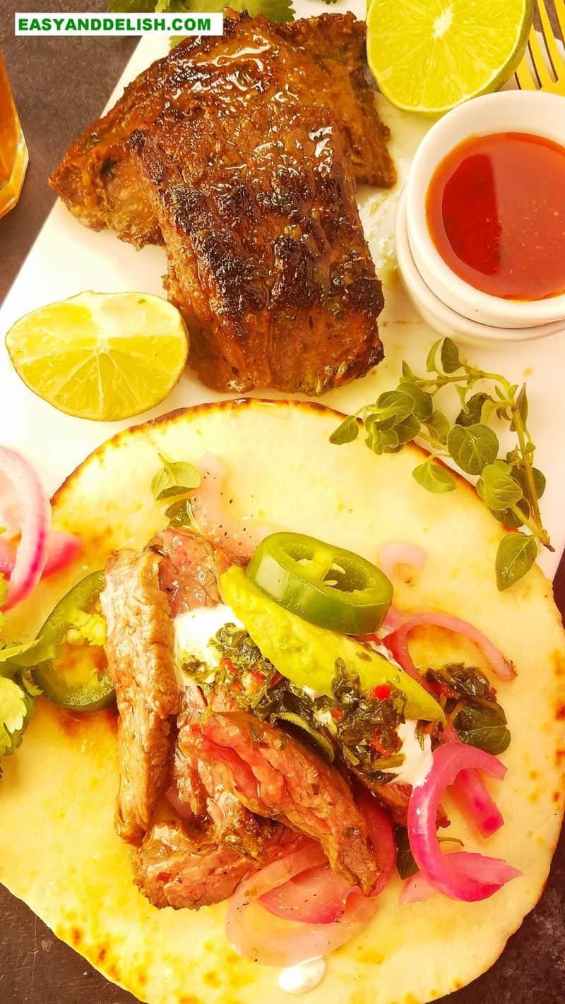 um tacos mexicano com carne e molho ao lado