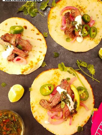 3 carne asada tacos on a surface with garnishes on the side