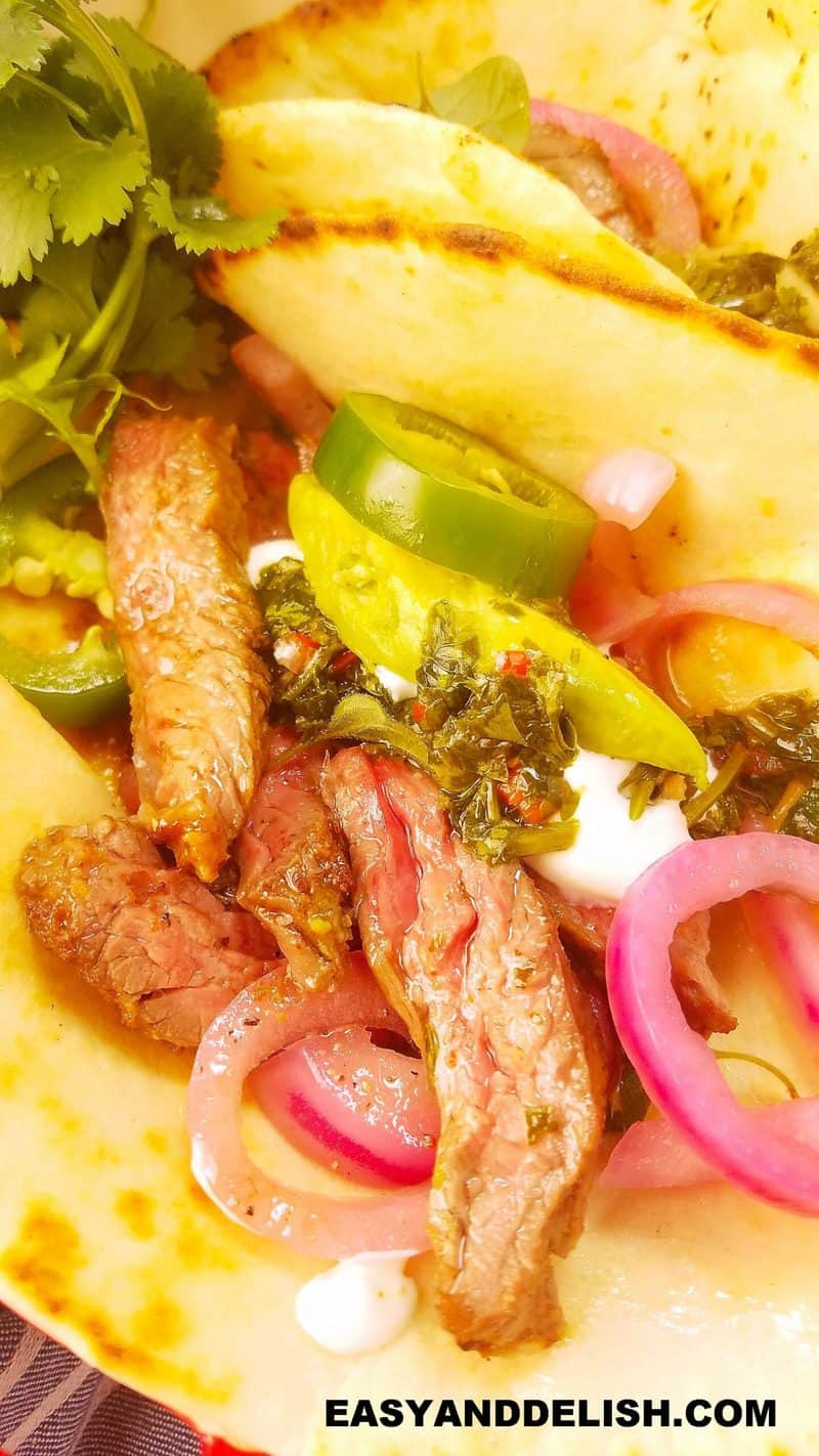 close of a taco with skirt steak and sides