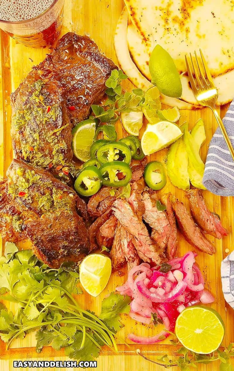 marinated skirt steak with chimichurri sauce and garnishes over a cutting board