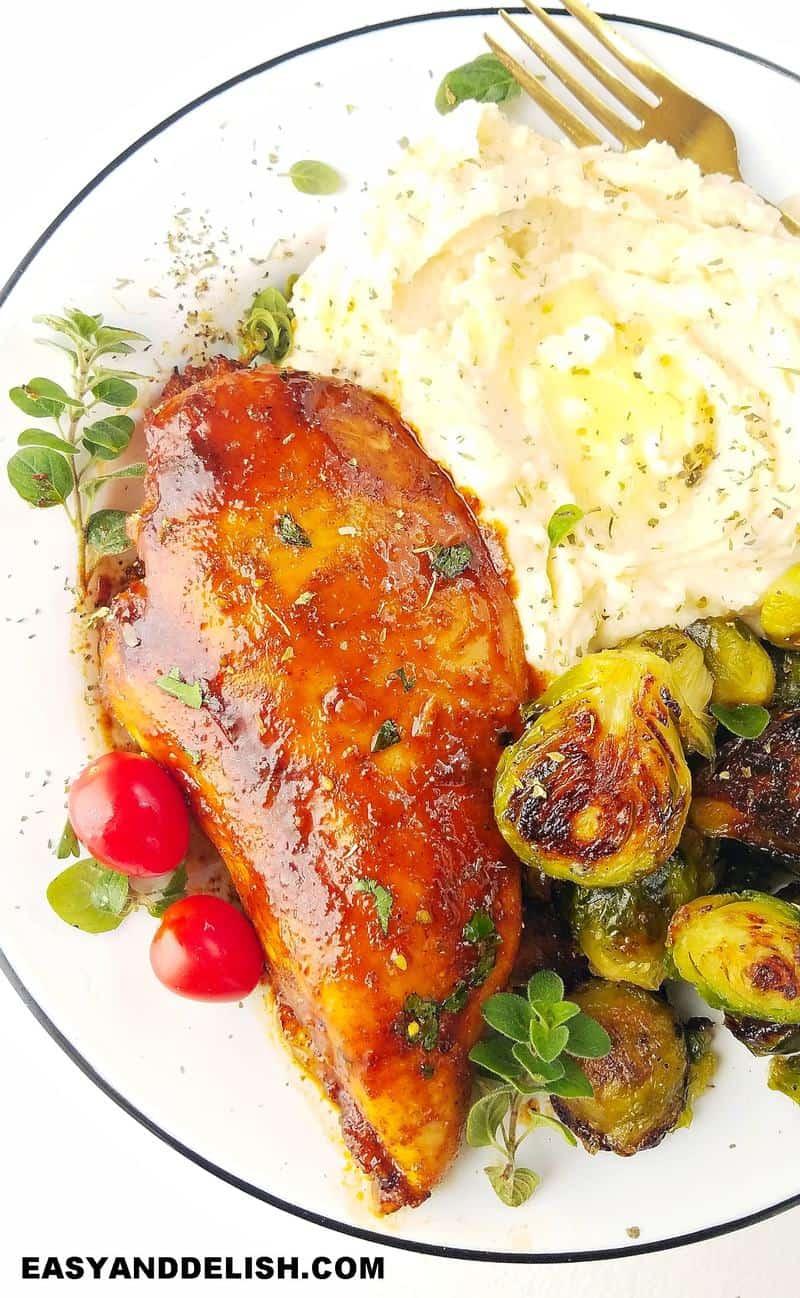 uma prato completo com pure de batatas, a ave cozinhada e couce de bruxelas