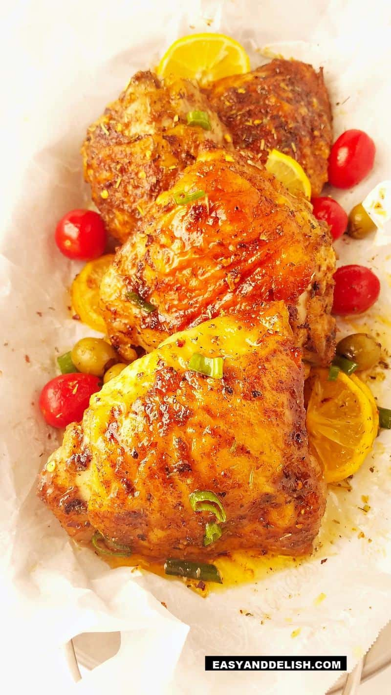 three baked chicken thighs in a platter with veggies on the side