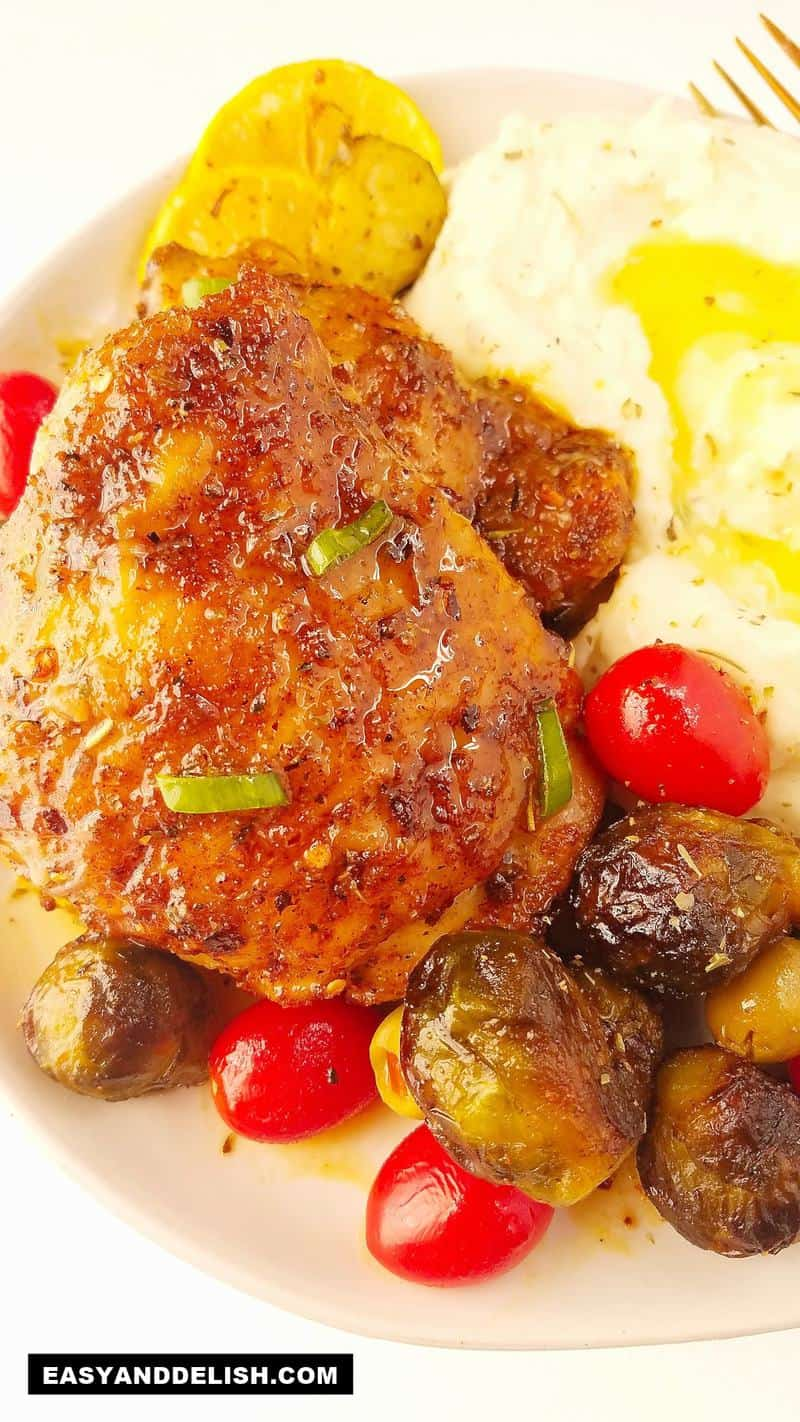 Bone in baked chicken thighs in a plate with mashed potatoes and roasted Brussels sprouts
