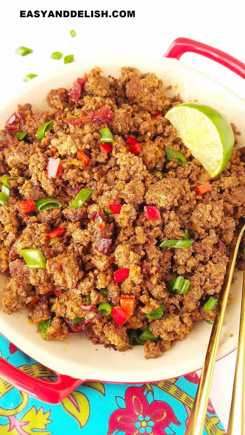 close up of a bowl of cooked ground beef topped with herbs and a lime wedge
