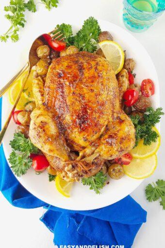 frango inteiro na panela de pressão servido em um prato com verduras ao lado
