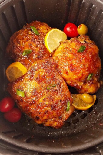 several chicken thighs in the air fryer with lemon slices