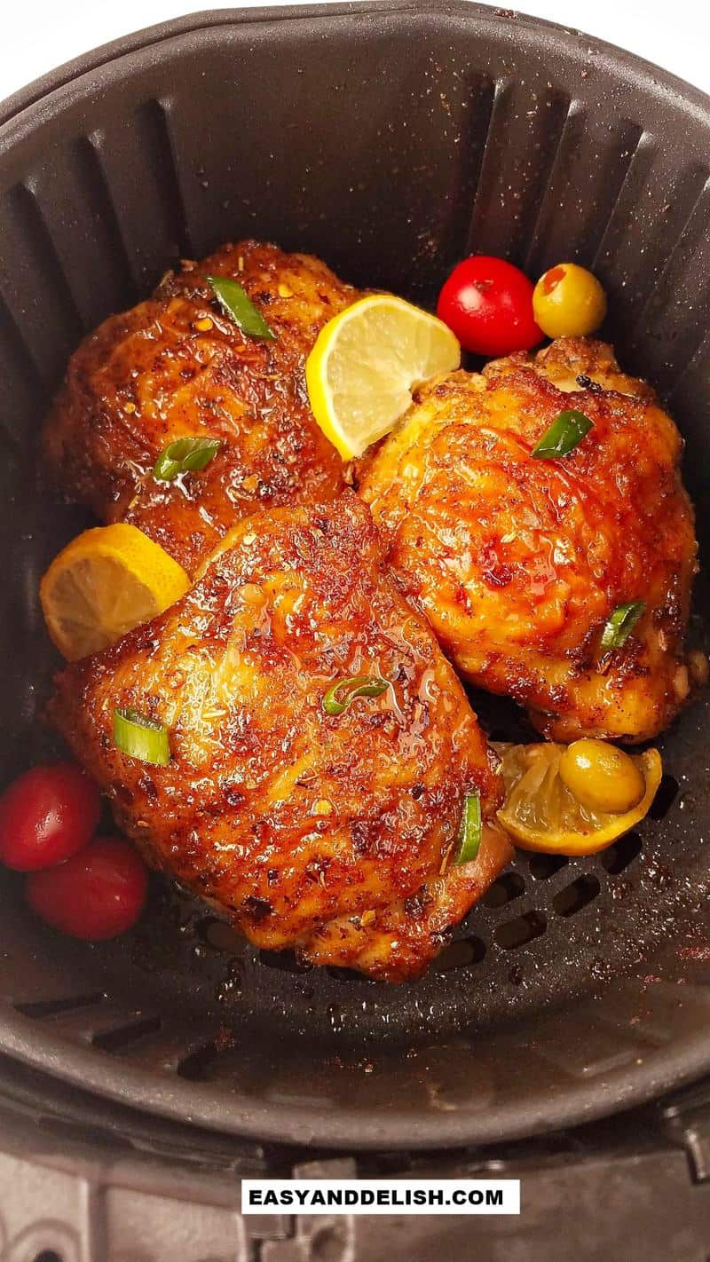 several chicken thighs in the ari fryer with lemon and veggies