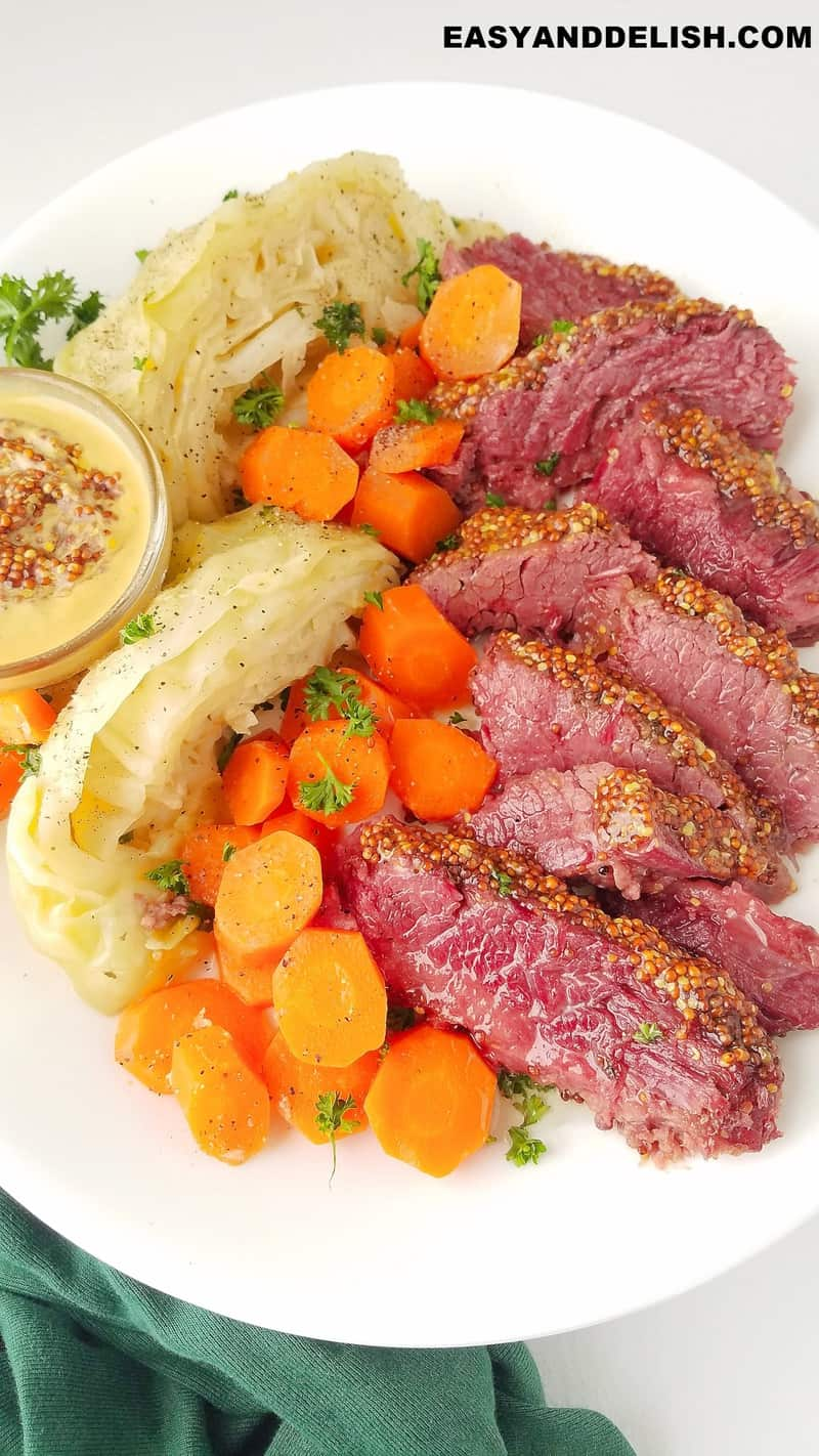 a platter with sliced corned beef and cabbage plus carrots