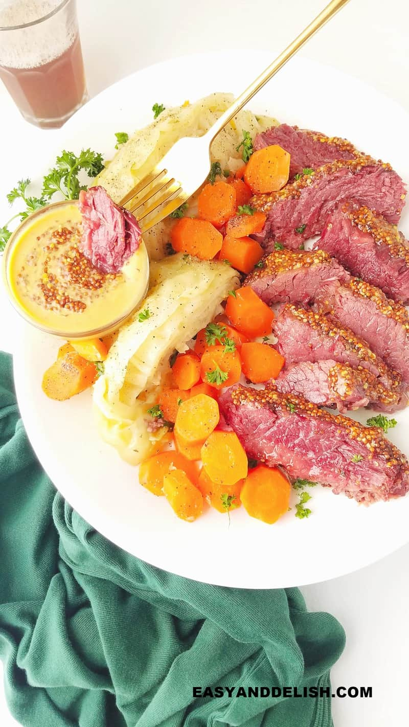 a piece of corned beef being dipped into a mustard sauce