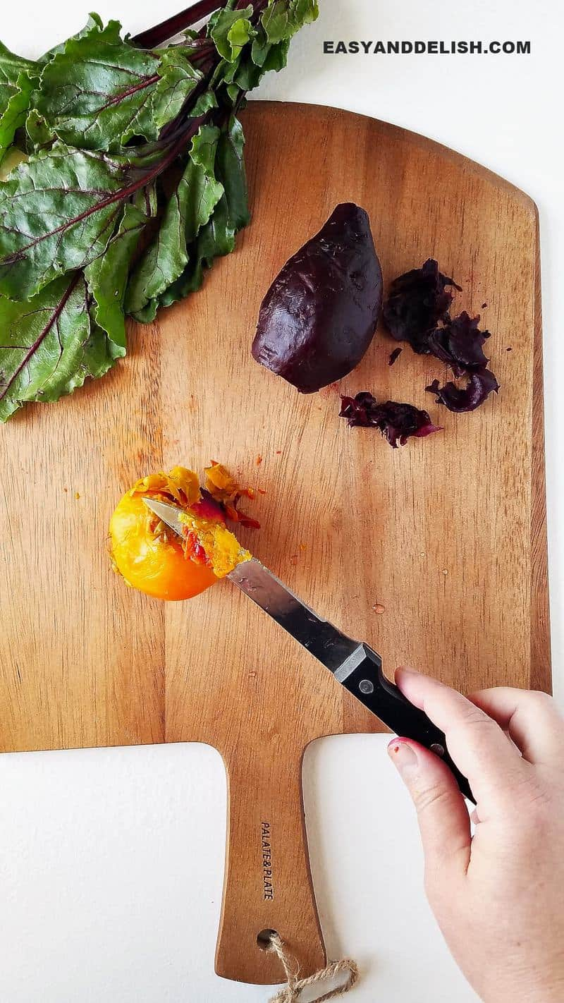 a knife peeling beets over a cutting board