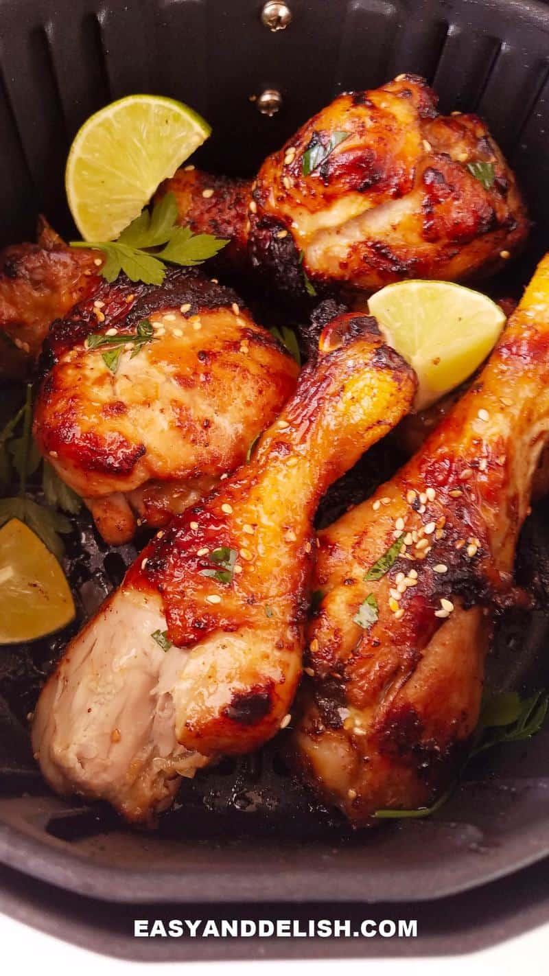 air fryer chicken drumsticks in air fryer tray with garnishes