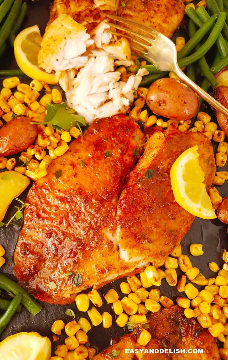 close up of a fried tilapia surrounded by veggies