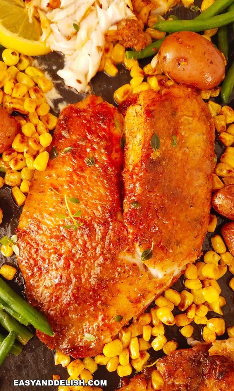 close up de um filé de tilapia na air fryer por cima de uma tábua com verduras