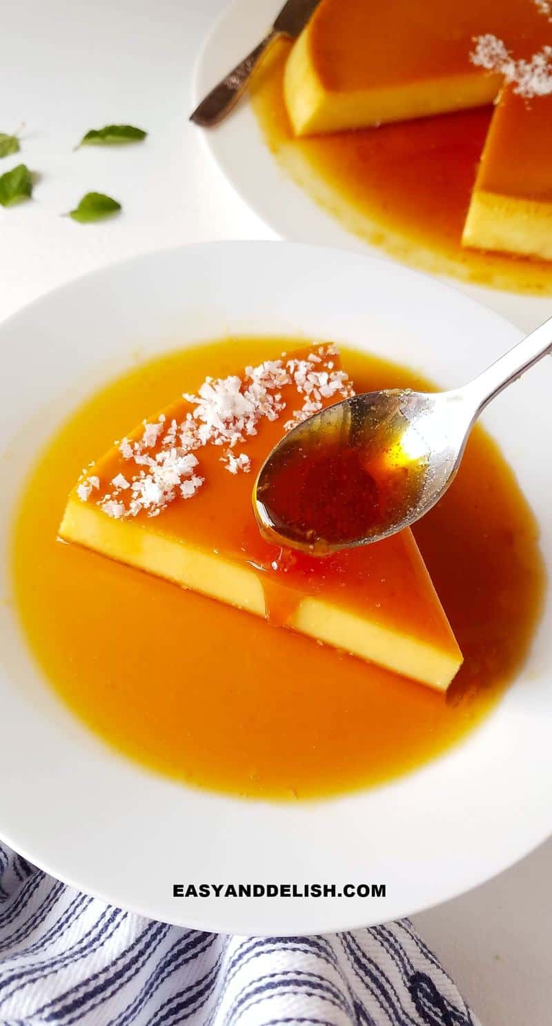 a spoon drizzling caramel over a slice of coconut flan