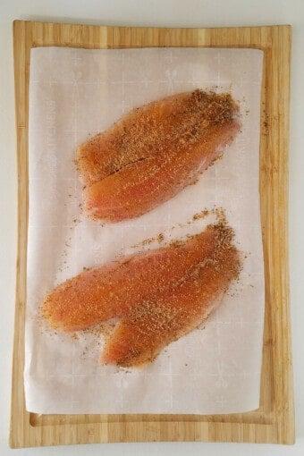 filés de tilápia temperados em cima de uma tábua de carne