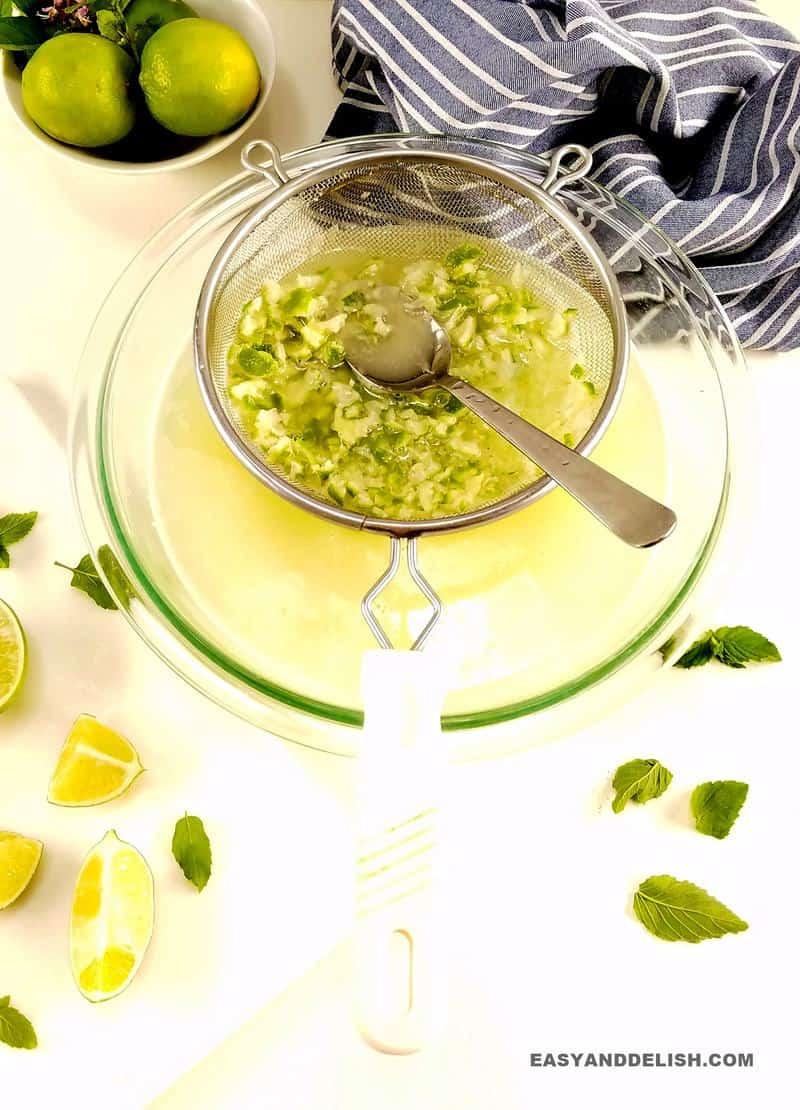 peneira com a polpa do limão sendo coada