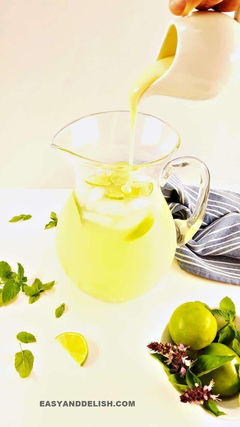 leite condensado sendo despejado em uma poncheira com limonada suíça