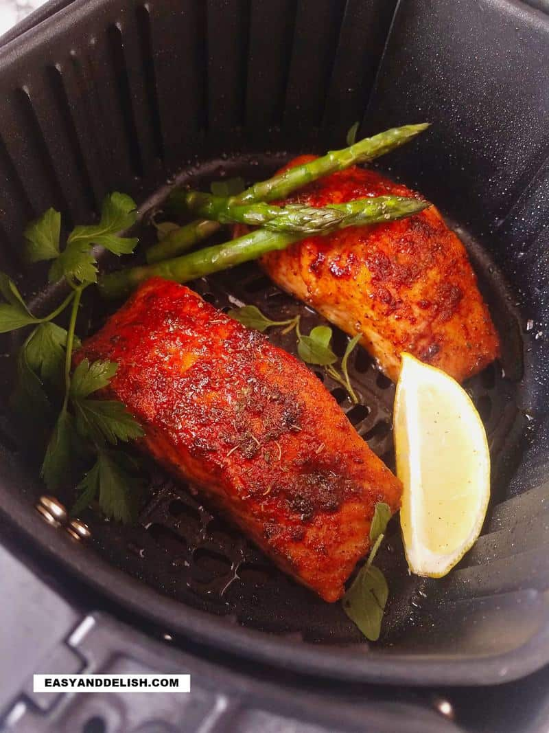 salmon in air fryer with lemon wedge and asparagus