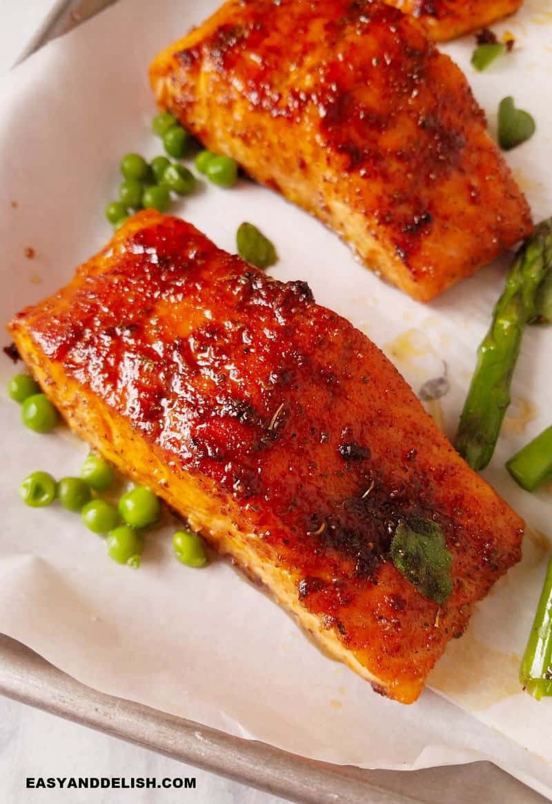 cooked fish with veggies resting in a baking sheet