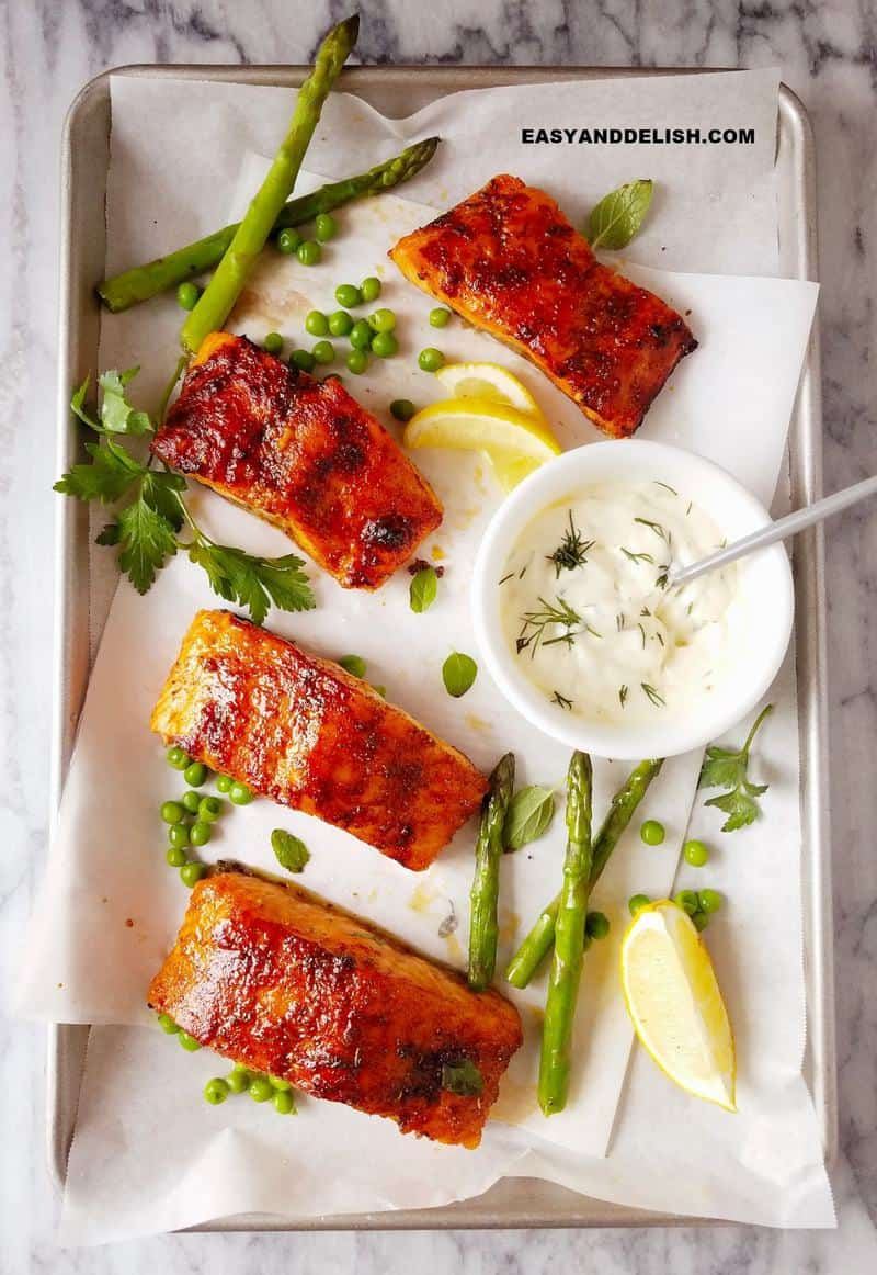 air fryer salmon filets in a baking sheet with veggies and sauce