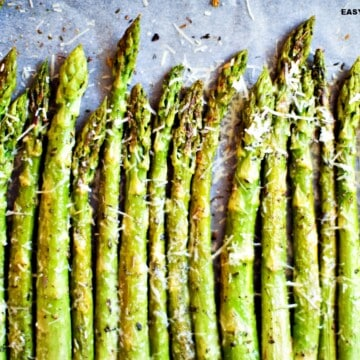 air fryer asparagus seasoned and lined up in a baking sheet
