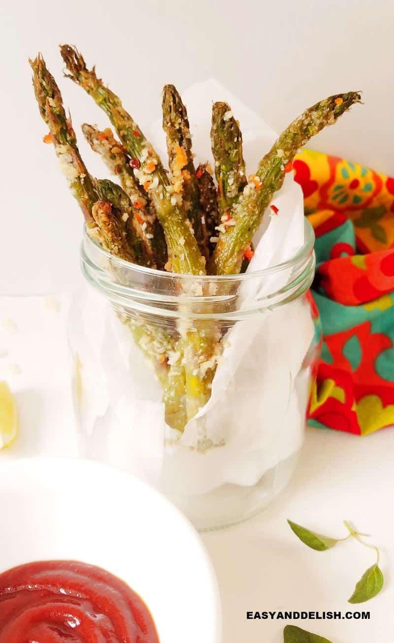 aspargos fritos em uma jarra com molho ao lado