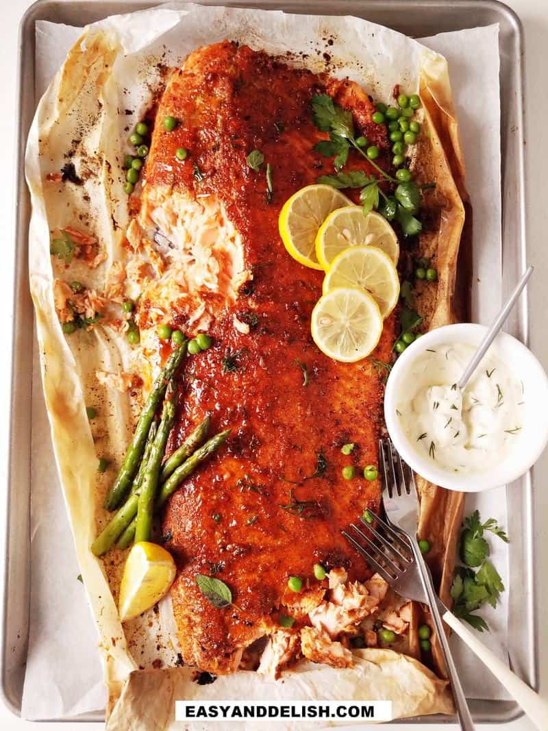 fish on a baking sheet with garnishes and sauce on the side