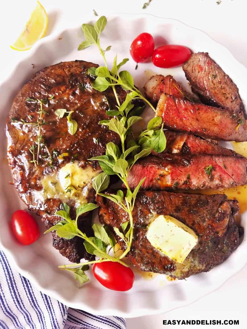 whole and sliced air fryer steak in a plate with garnishes on top