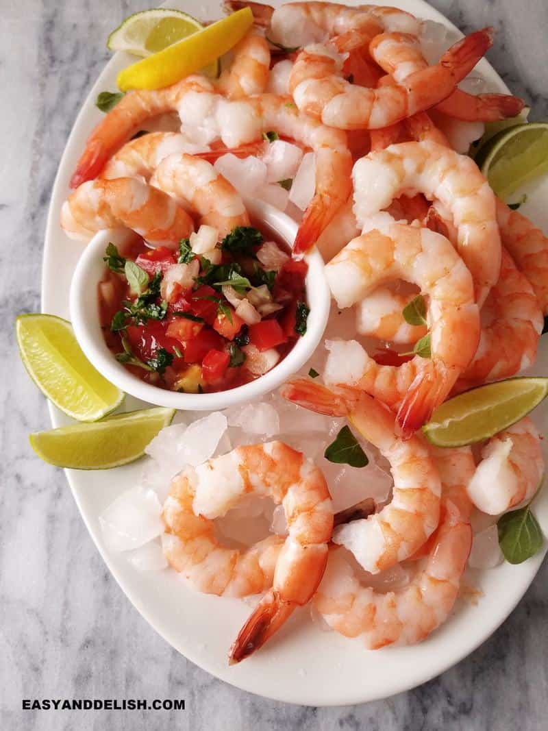 close up of a platter of Mexican shrimp cocktail with salsa in a bowl