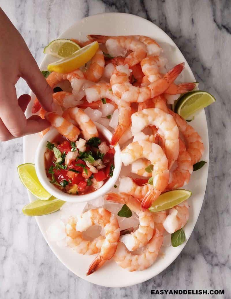coctel de camarones in a platter and a hand dipping a shrimp into the salsa