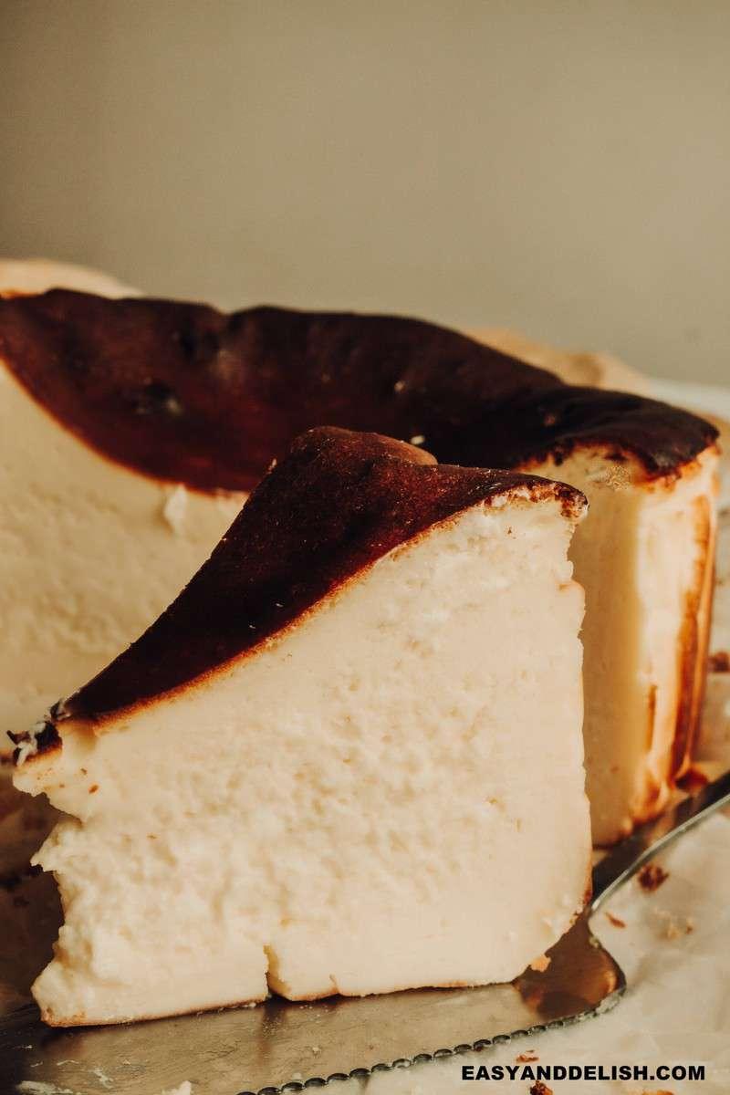 close up de uma fatia de torta de queijo basca com o resto da torta atrás