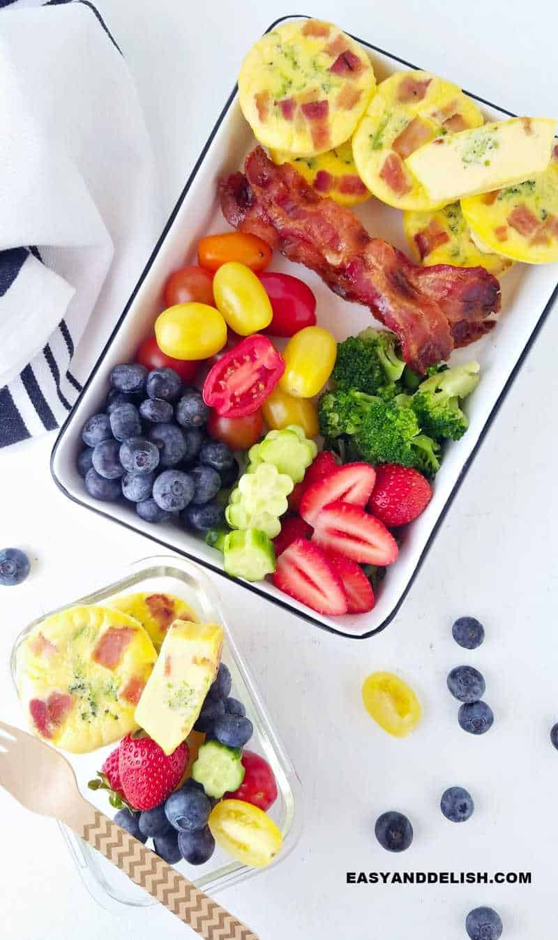 2 meal prep containers with breakfast muffins plus bacon, fruits and veggies